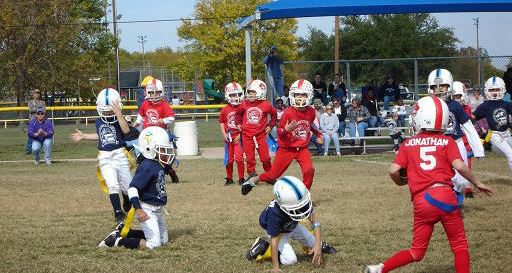 Children Playing Flag Football Wearing Helmets and Uniforms